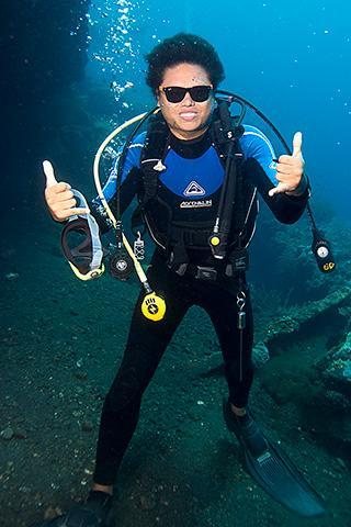 scuba diver underwater tulamben wreck bali indonesia wicked sunfish mola sign sunglasses vertical 320px
