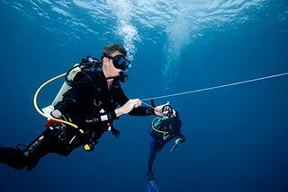 scuba divers underwater padang bai bay bali indonesia safety stop help buddy team reel line 320px